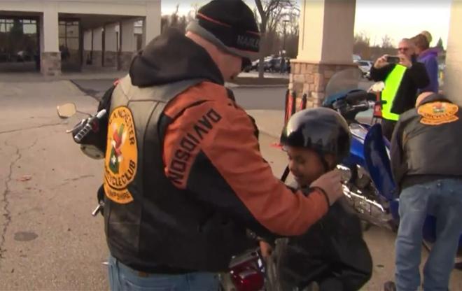 Člen motorkářského klubu předávající helmu malému chlapci | Foto: CBS